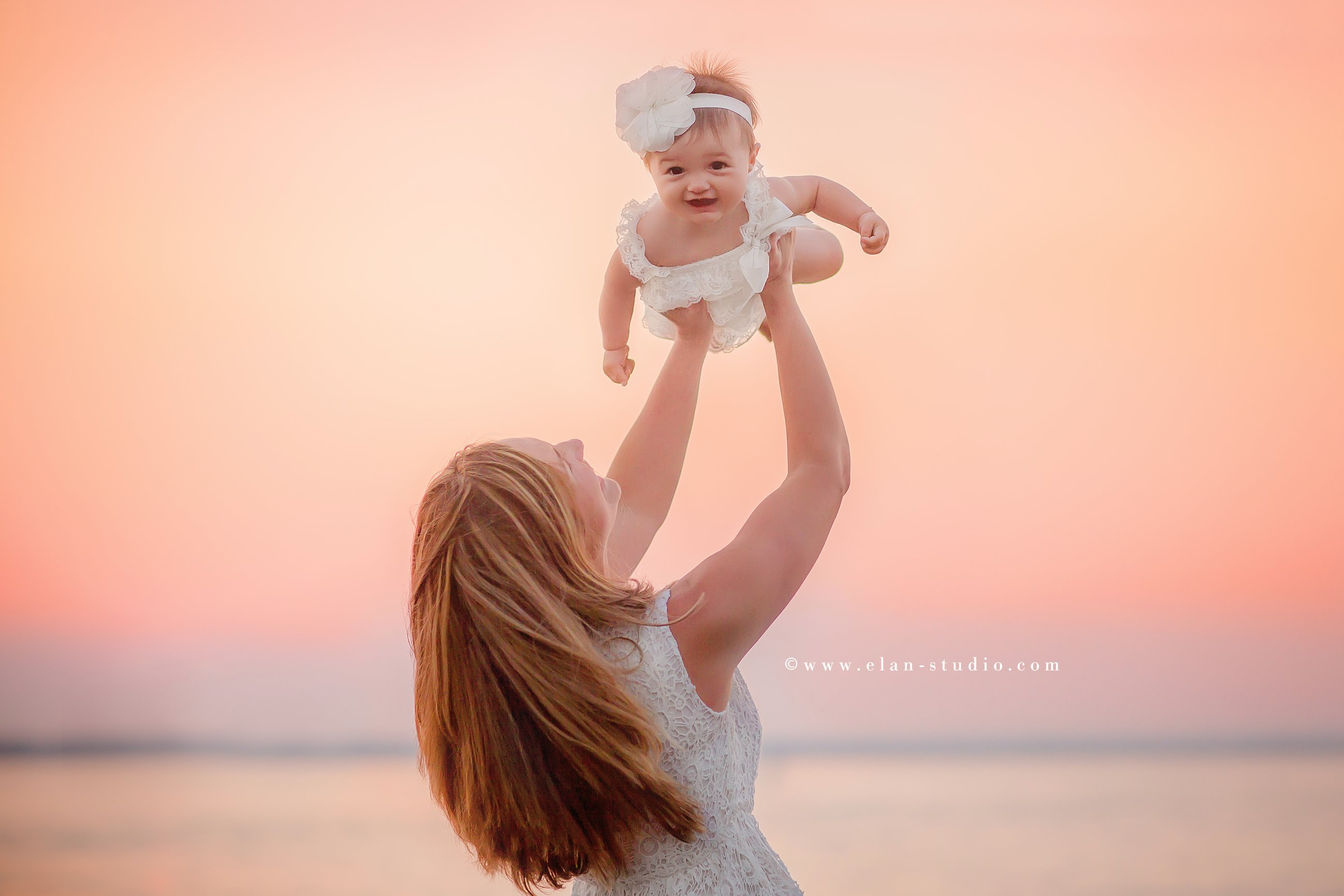 mother twirling with baby daughter smiling at camera