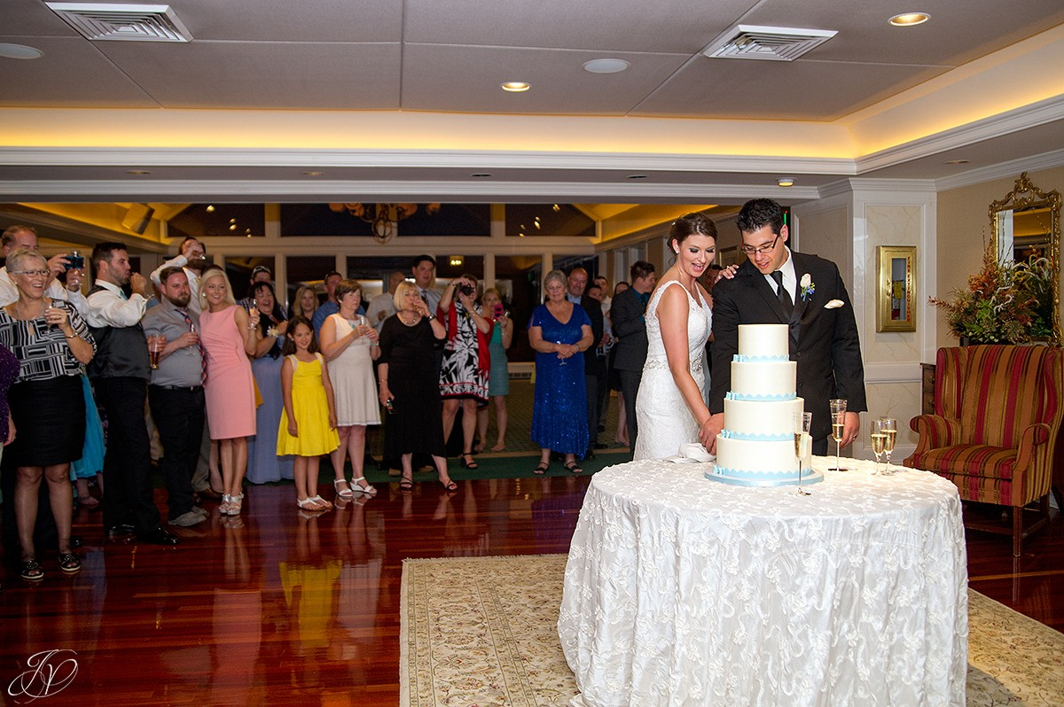 bride and groom cutting the cake at reception
