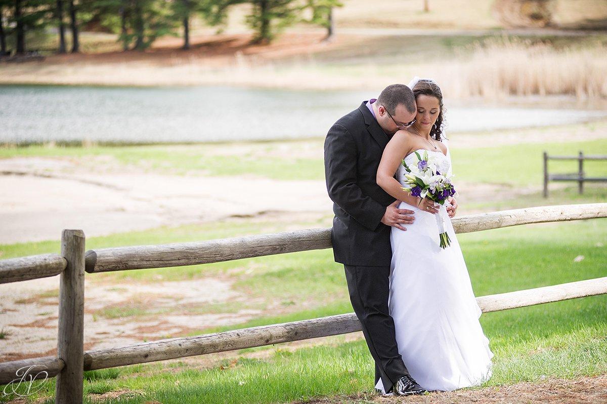 photo of groom kissing bride on shoulder