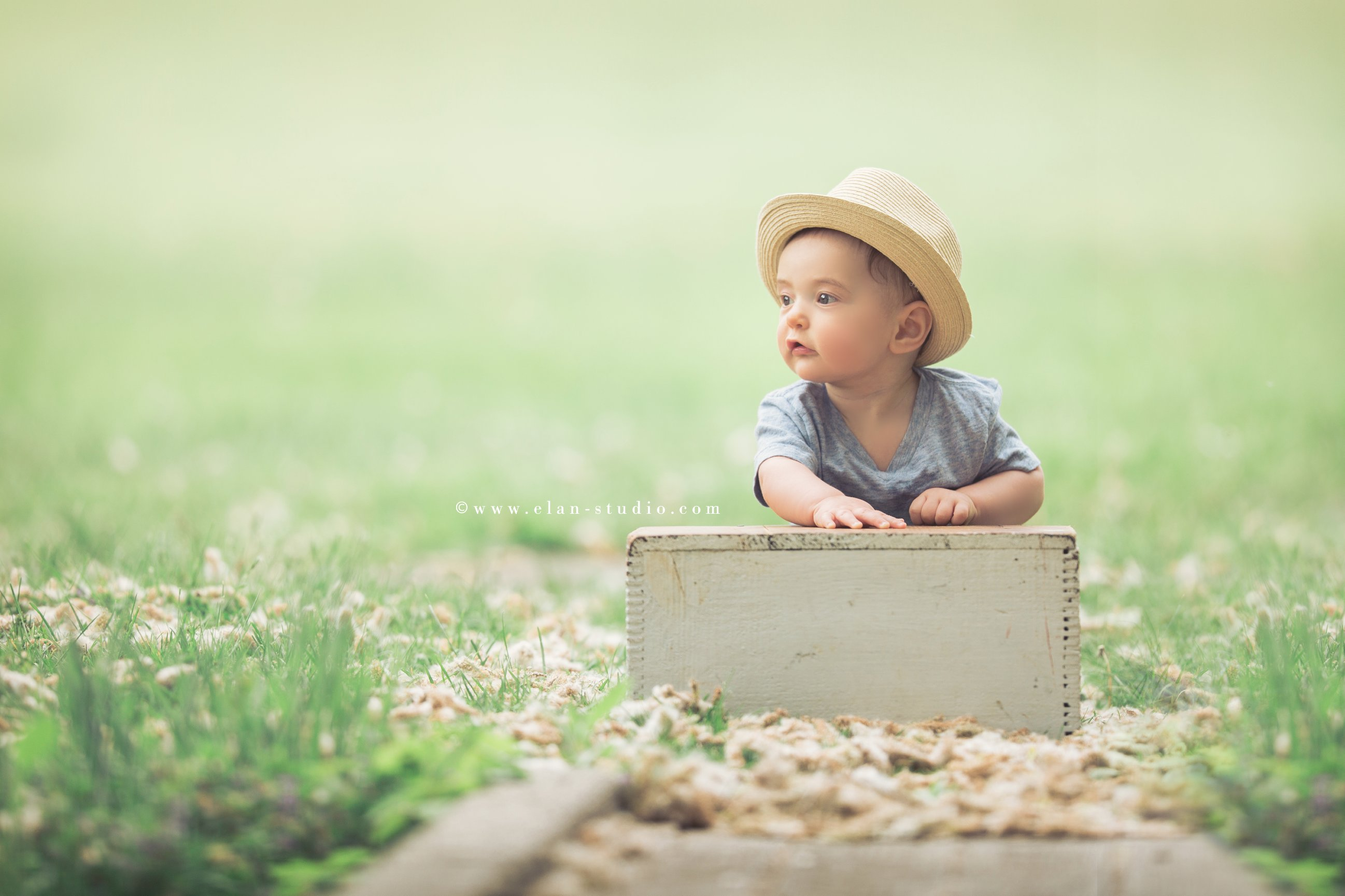 sitting baby boy wearing straw hat and blue chambray shirt