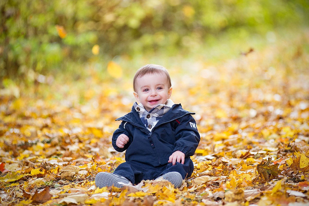 adorable one year old playing in leaves