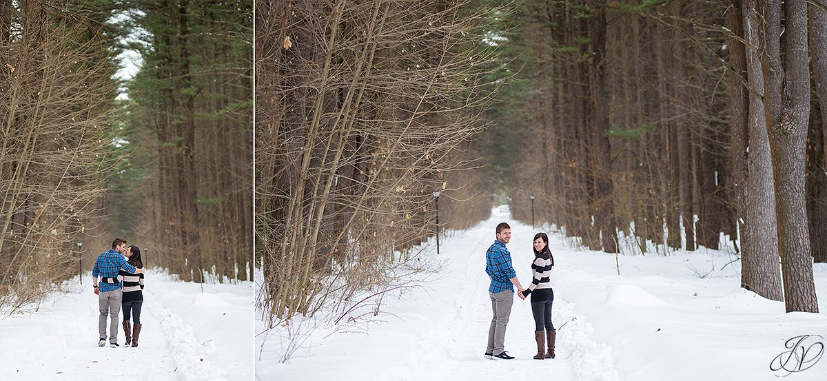 engaged couple walking in trees in winter