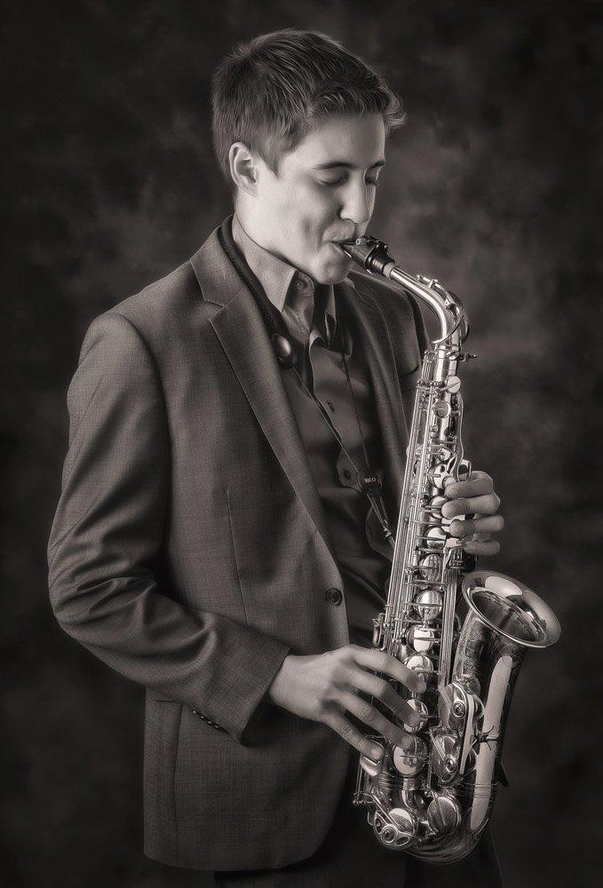 High school senior portrait featuring a band instrument in a San Antonio portrait studio