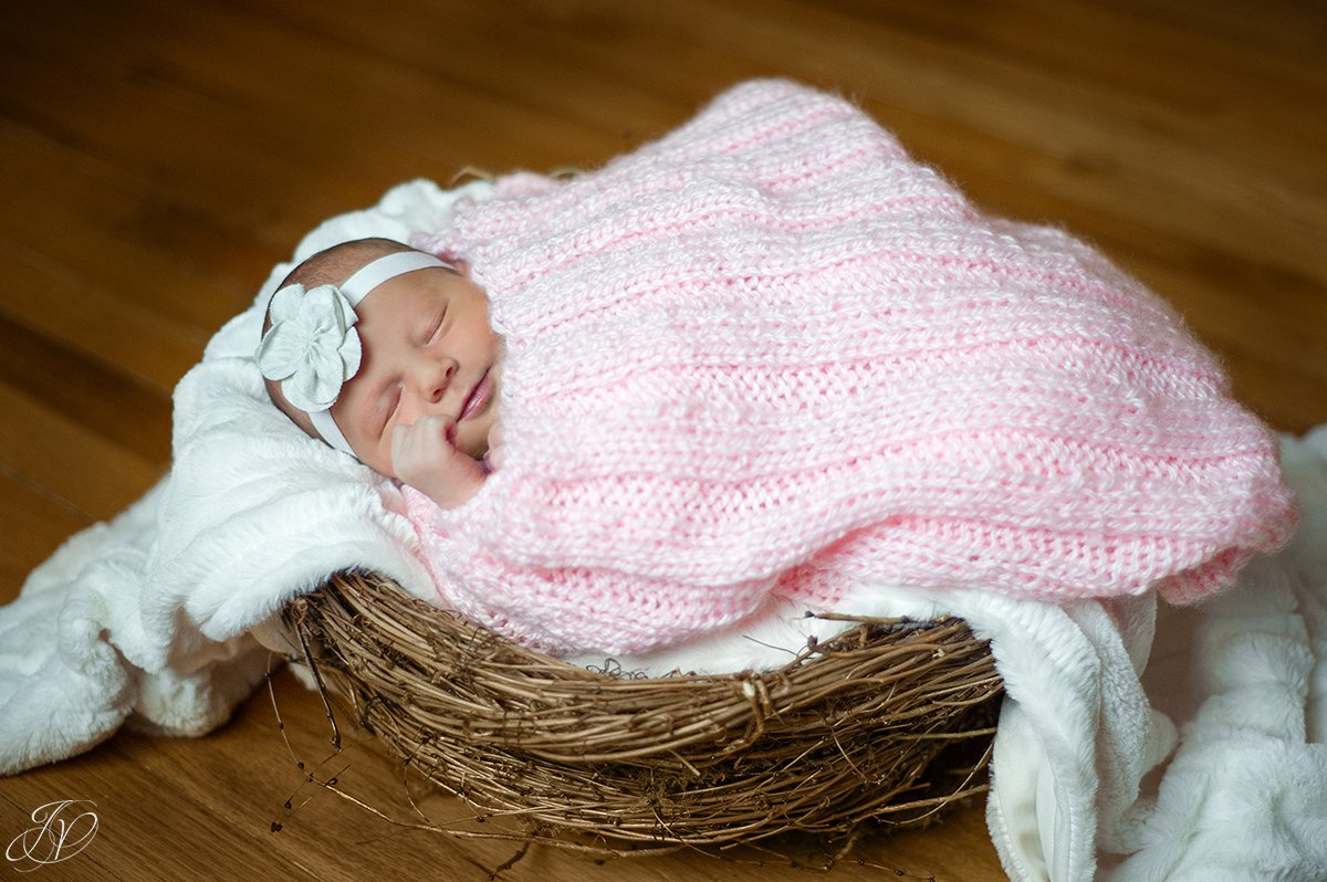 photo of newborn in basket smiling