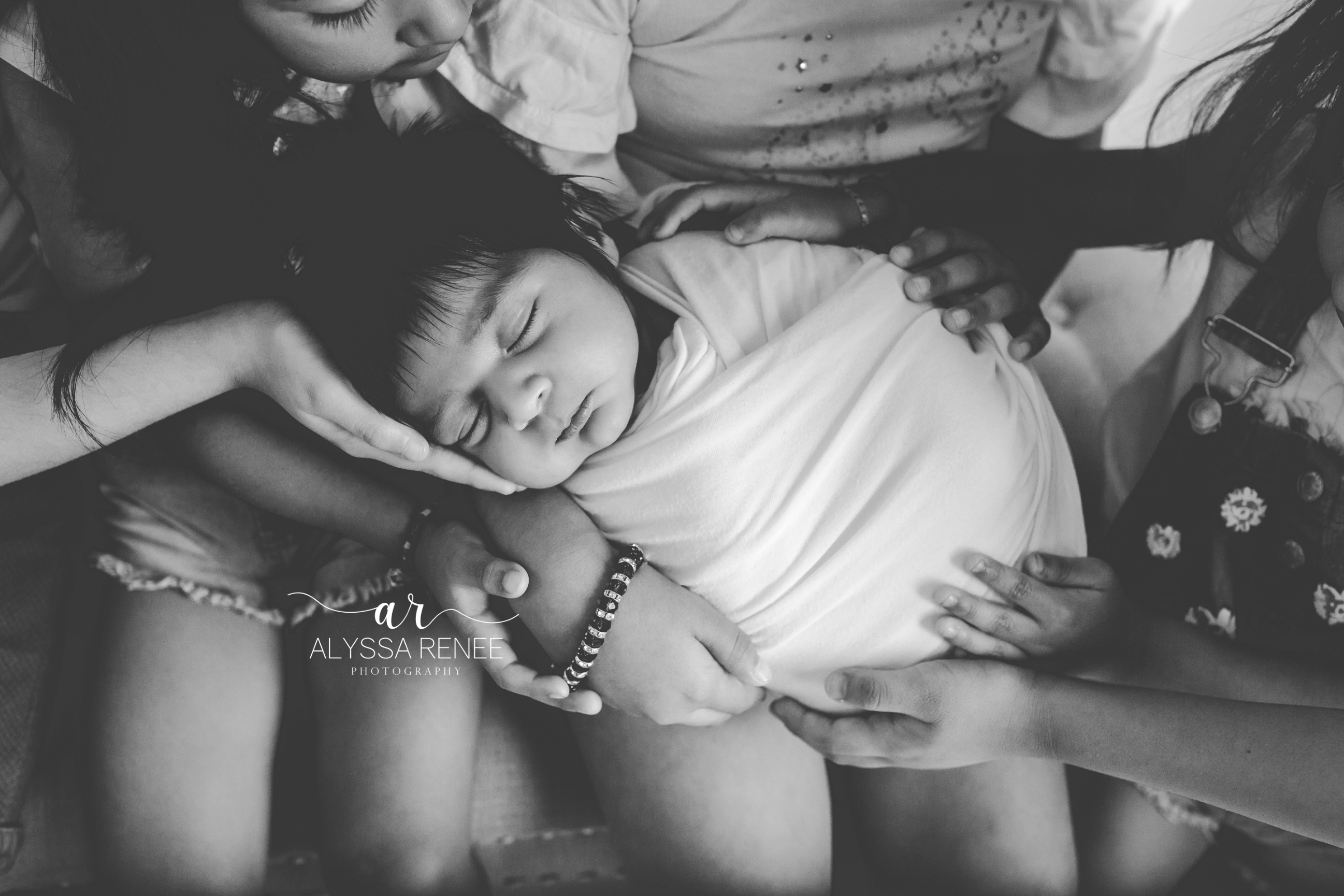 Black and white image of newborn close up with siblings hands surrounding baby