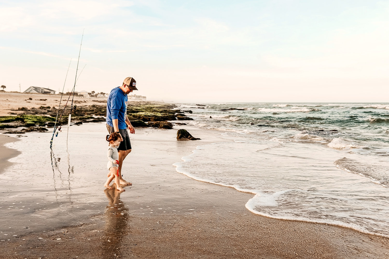father and daughter walking into the waves on a Florida beach, fishing poles in background